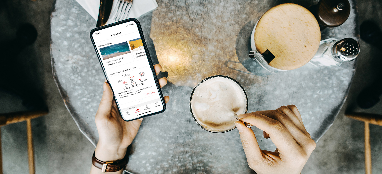 bird's eye view of person drinking coffee and using a mobile app