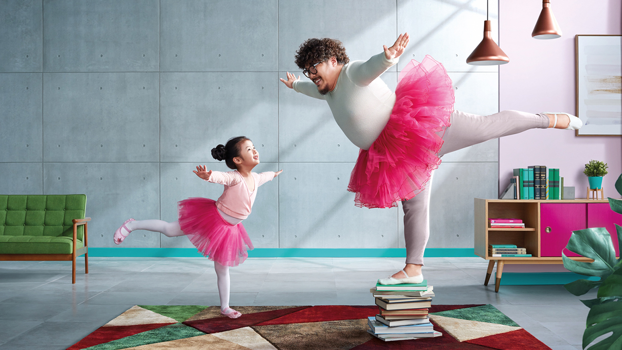 Dad and his daughter are dressing up in ballet costumes and performing at home; image used for HSBC FirstSave Insurance Plan.