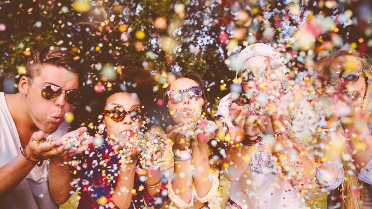 Hipsters blowing confetti; image used for earning online spending rewards.