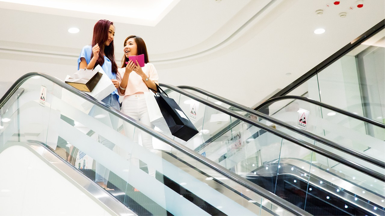 Two women are on an escalator in shopping mall; image used for HSBC Card Rewards.