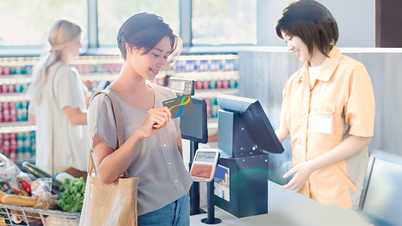 A woman is using her octopus card for payment; image used for HSBC Octopus Automatic Add Value Services.