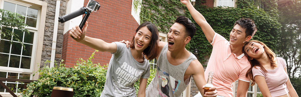Two couples are taking selfie outside; image used for HSBC Visa Gold Card.