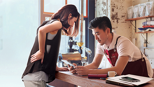 A couple is using mobile phone; image used for HSBC Advance page.