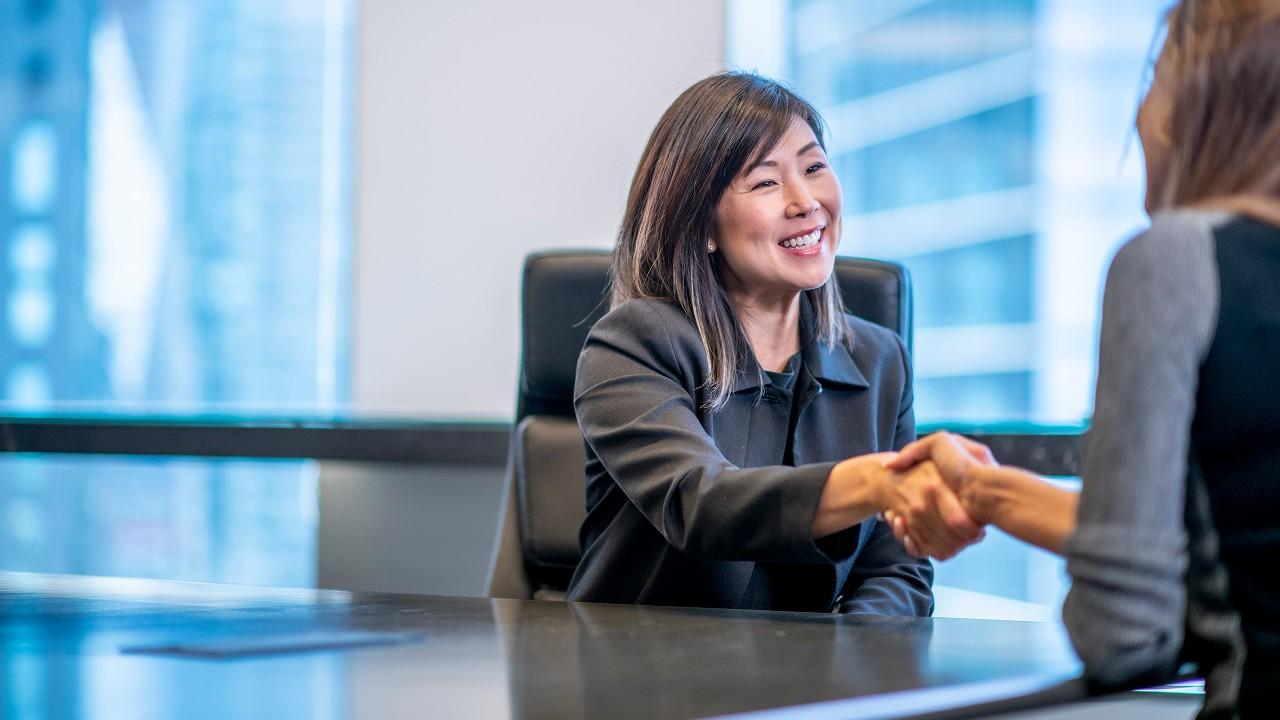 A business-woman shaking hand with her client; image used for account services.