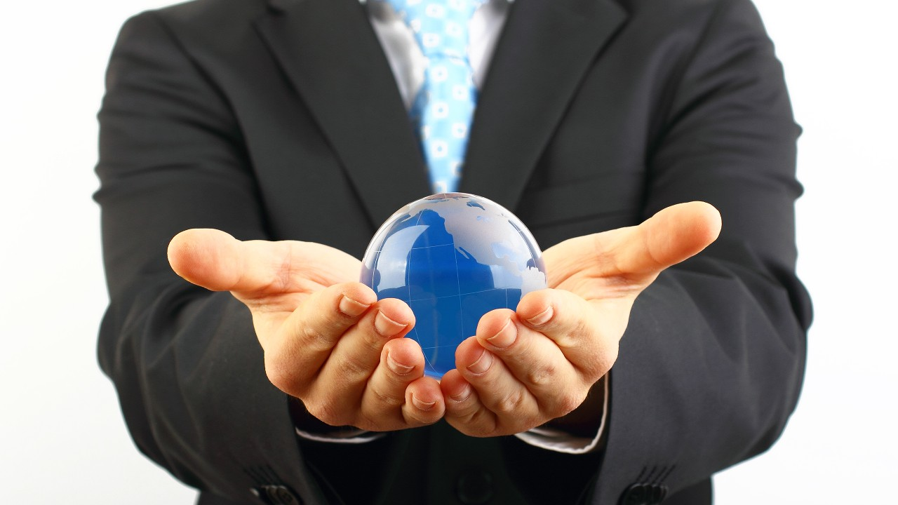 A business man holding a globe made by glass; image used for  Over-the-counter Traded Debt Securities / Certificates of Deposit (CDs)