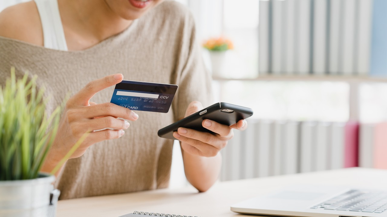 A lady is paying credit card by using her mobile phone; image used for HSBC Credit Card.