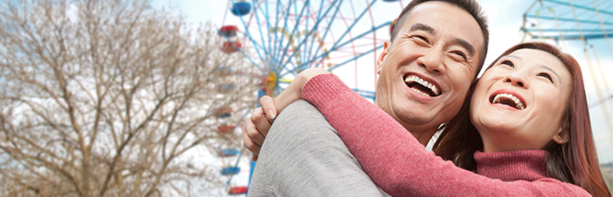 A couple is hugging under the ferris wheel; image used for EarlyIncome Annuity Plan.