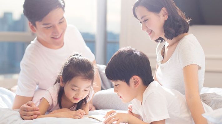 Happy family is reading books in bed; image used for Income Goal Insurance Plan.