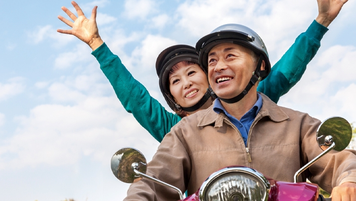 Couple are riding motor cycle in excitement; image used for HSBC EarlyIncome Annuity Plan