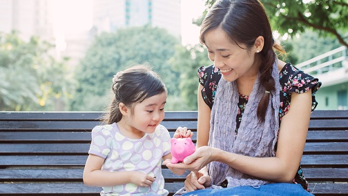 Smiling mother holding a piggy bank with her daughter putting money in; image used for HSBC Wealth Management Protection page.