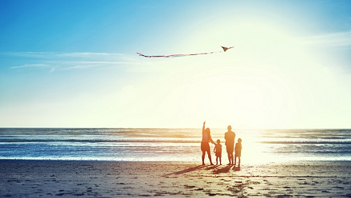 A family flying a kite together by the beach; image used for HSBC Wealth Management The Power of Protection page.