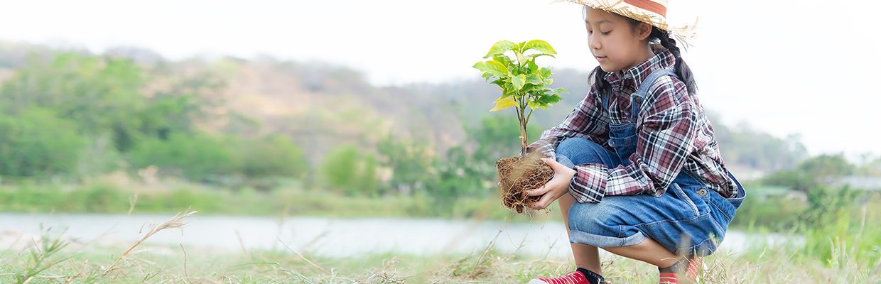 A girl is planting a tree; image used in ESG investment products