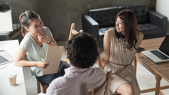 Three people are talking together; image used for loans product.
