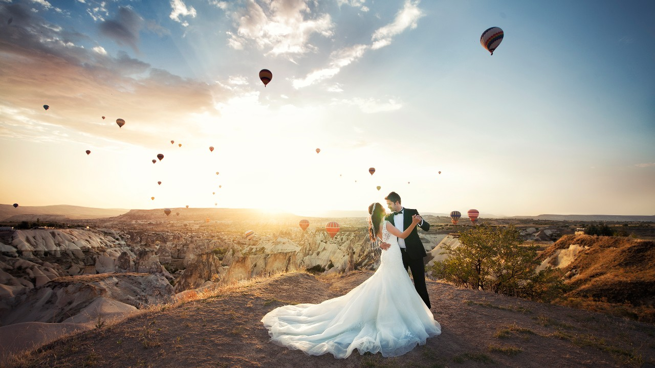 "A couple is wearing their wedding dress and dancing in the mountain, image used for ""Destination wedding planning"" article"