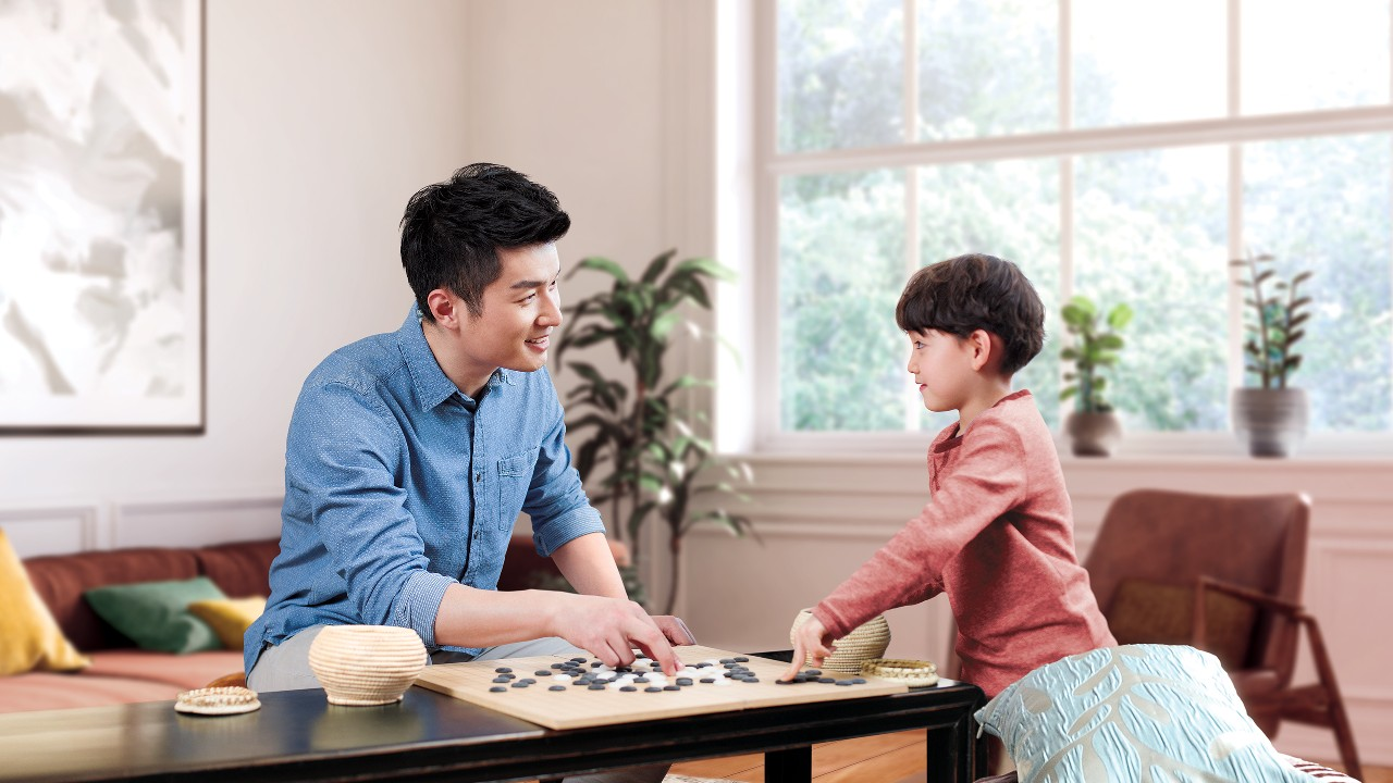 Father and son are playing Go; image used for Personal Instalment Loan Balance Consolidation Program.