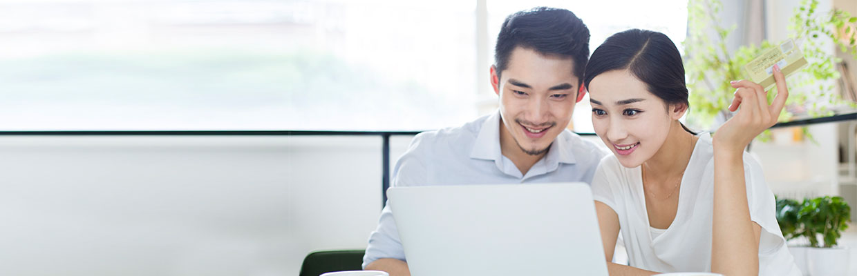 "A couple is checking their laptop, image used for ""5 Factors to consider before applying for a loan"" article"