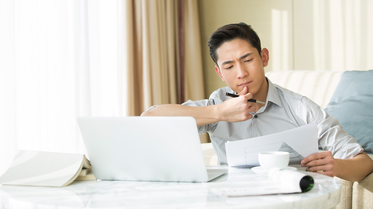 "A man is thinking and planning his project, image used for ""Factors to consider before applying for a loan"" article"