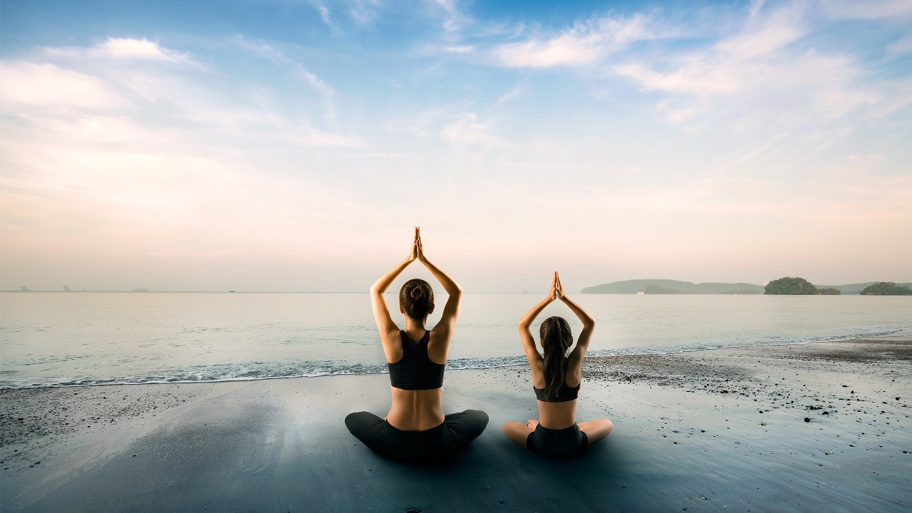 "Two women is doing yoga on the beach, image used for ""Great things to do on your family summer vacation"" article"