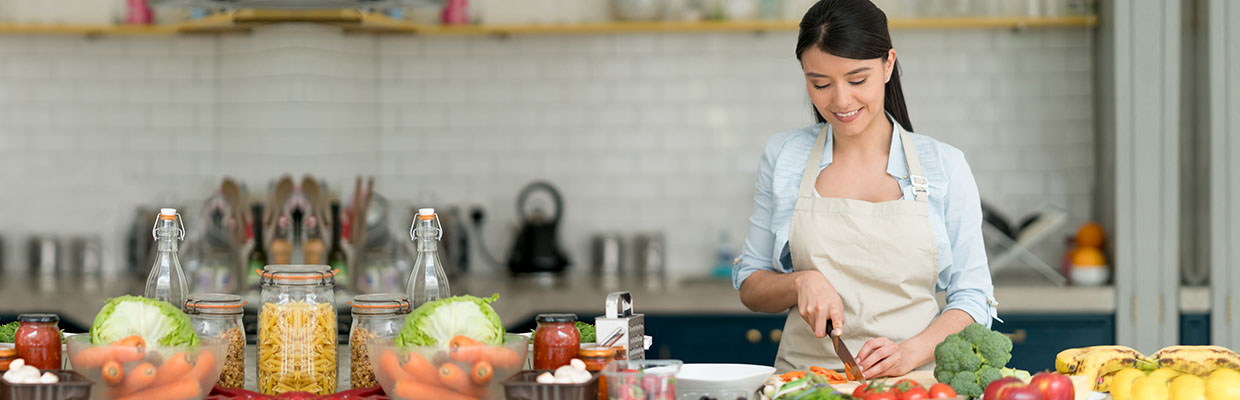 "A woman is cooking in the kitchen, image used for ""How much does it cost to become a master chef"" article"