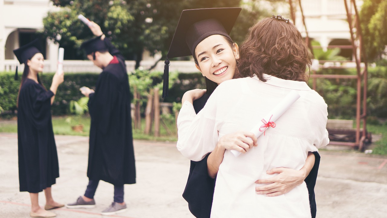 "Daughter is hugging her mother in graduation ceremony, image used for ""Important things to consider when studying abroad"" article"