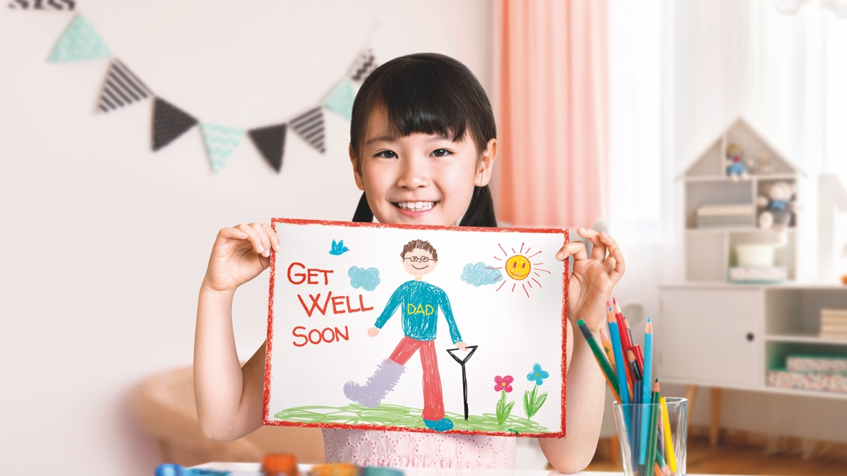 Daughter holding up a 'get well soon' card for her father