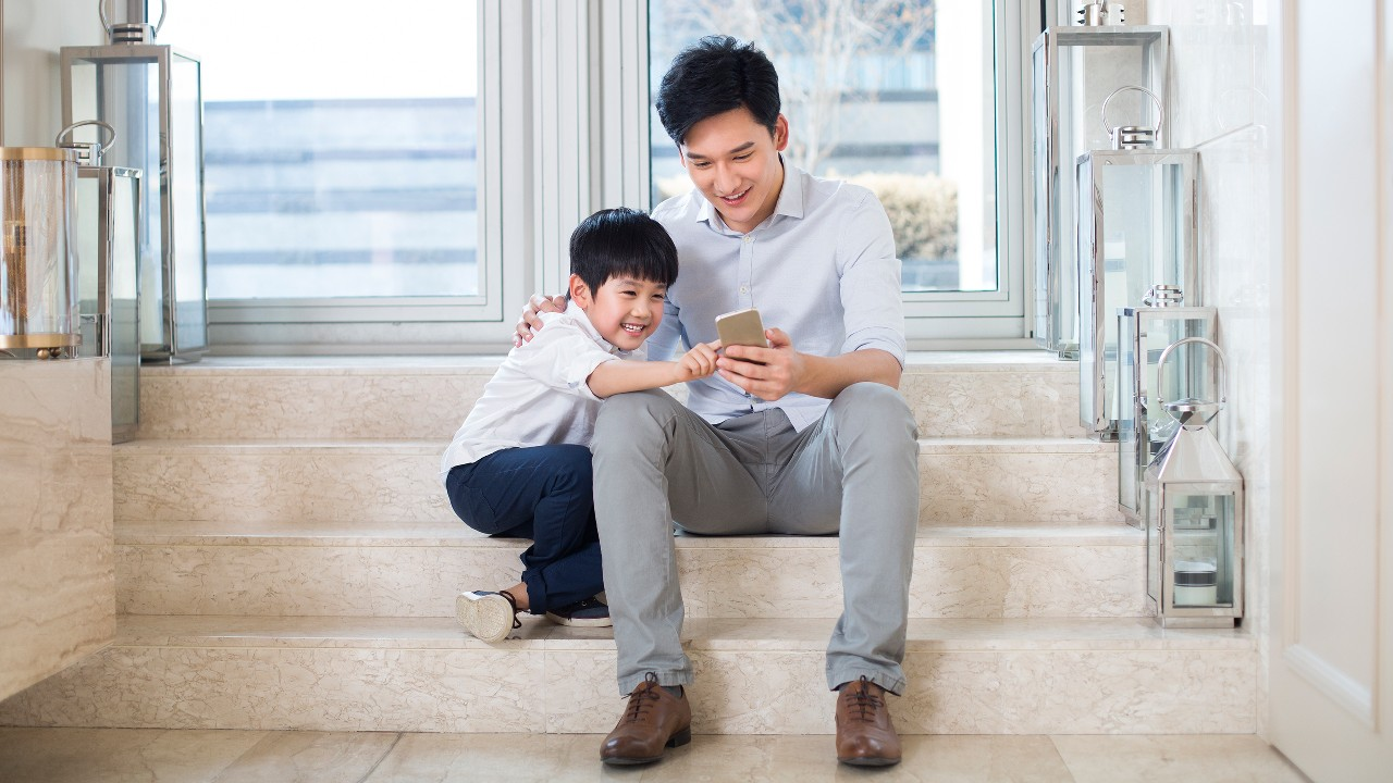 Father and son using mobile phone together; image used for navigation to banking security pages.