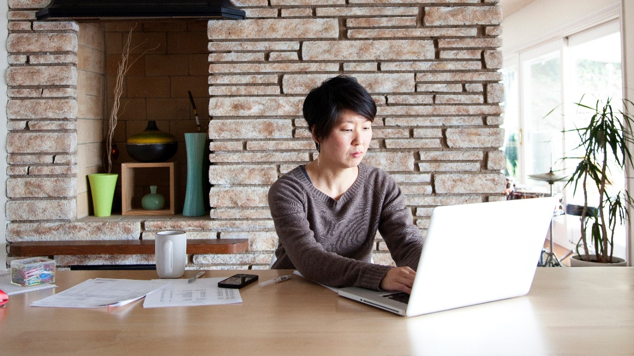 A woman is making a funds transfer from her laptop at home; image used for HSBC autoPay