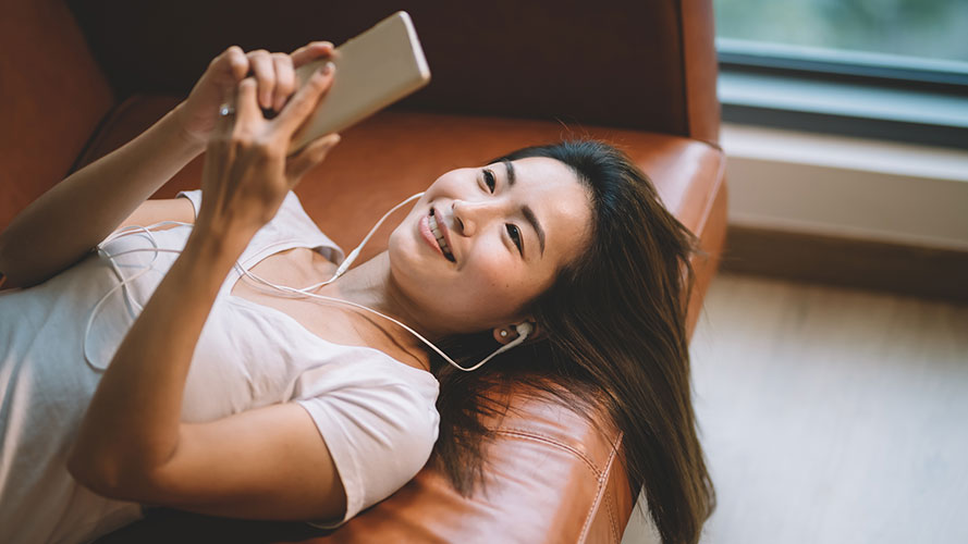 Woman lying on sofa listening to music; image used for HSBC account opening offer