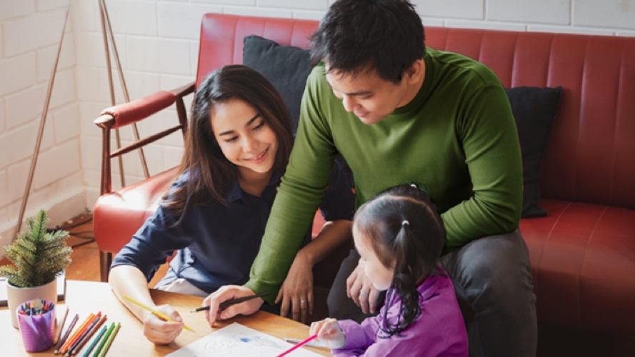 Young parents and daughter drawing in living room; image used for HSBC Life insurance policies