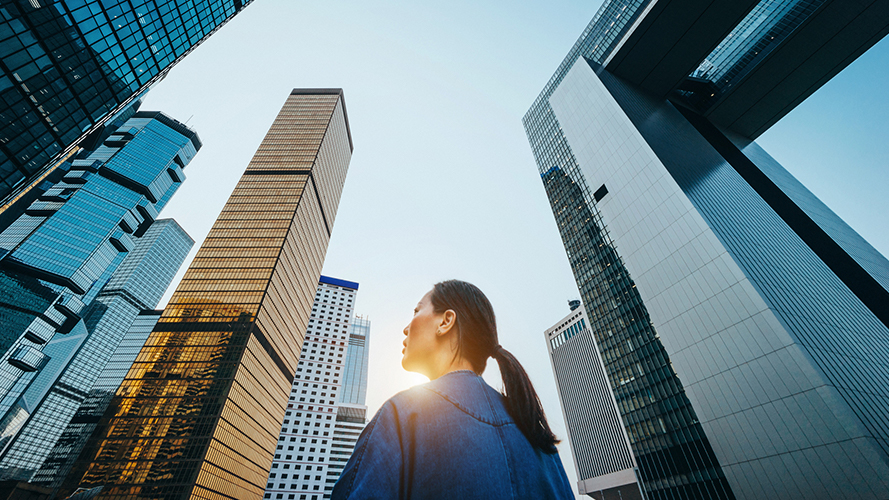 Woman looking up at skyscrapers in a city; image used for HSBC Wealth Insights Hub